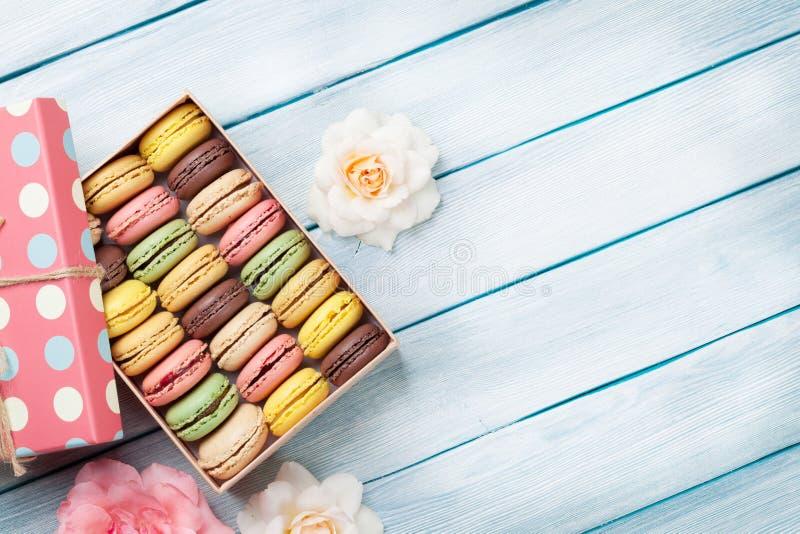 Macarons colorés dans un boîte-cadeau et des roses photos stock
