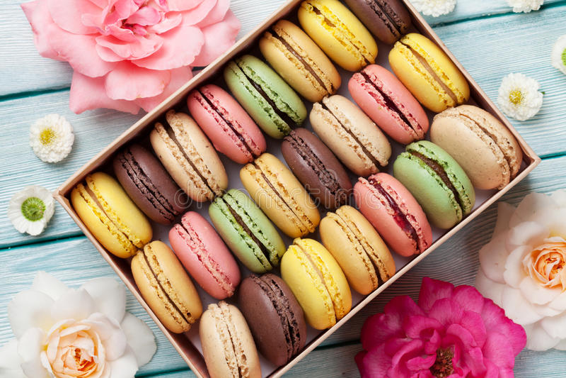 Macarons colorés dans un boîte-cadeau et des roses image libre de droits