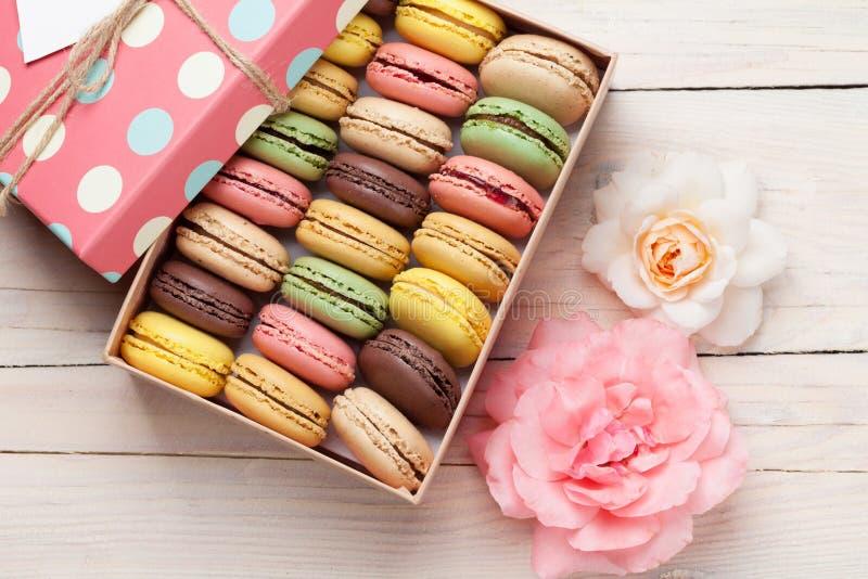 Macarons colorés dans un boîte-cadeau et des roses photographie stock