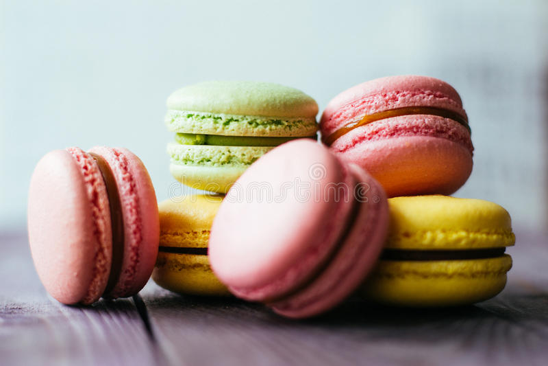 Macarons coloreados cocidos frescos de las galletas de los pasteles de los macarrones, macarrones en un cierre blanco de la placa imagenes de archivo