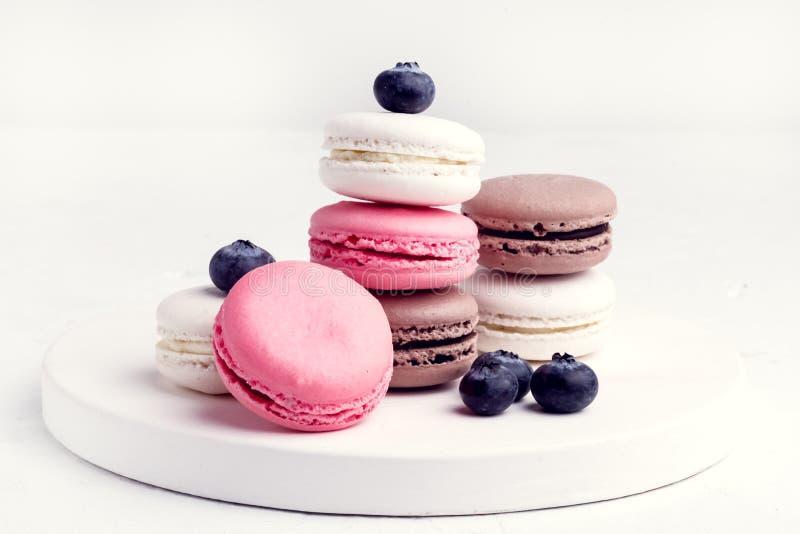 Macarons colorido francês Macarons pastel colorido no rosa branco de Whitr do fundo e Brown Macaron com mirtilo fresco foto de stock
