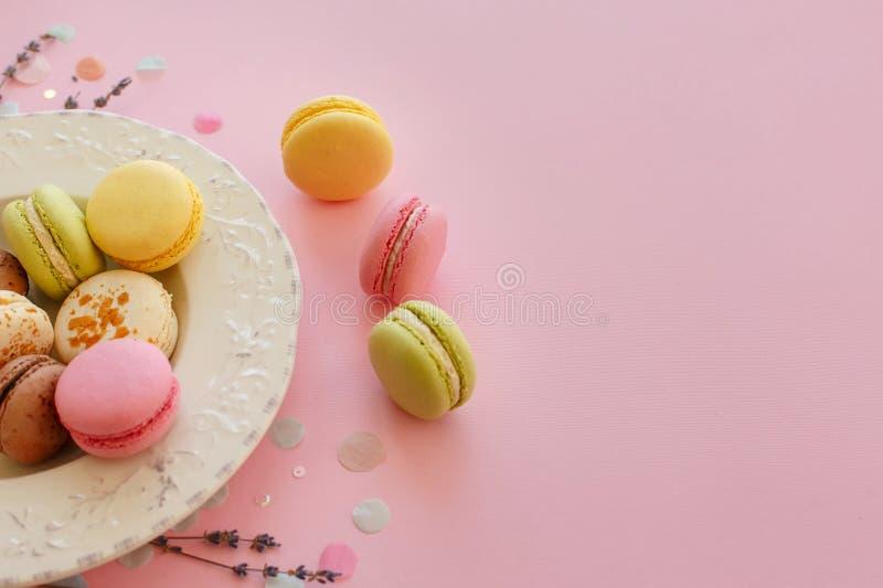 Macarons coloridos saborosos na placa do vintage no rosa pastel na moda p fotos de stock