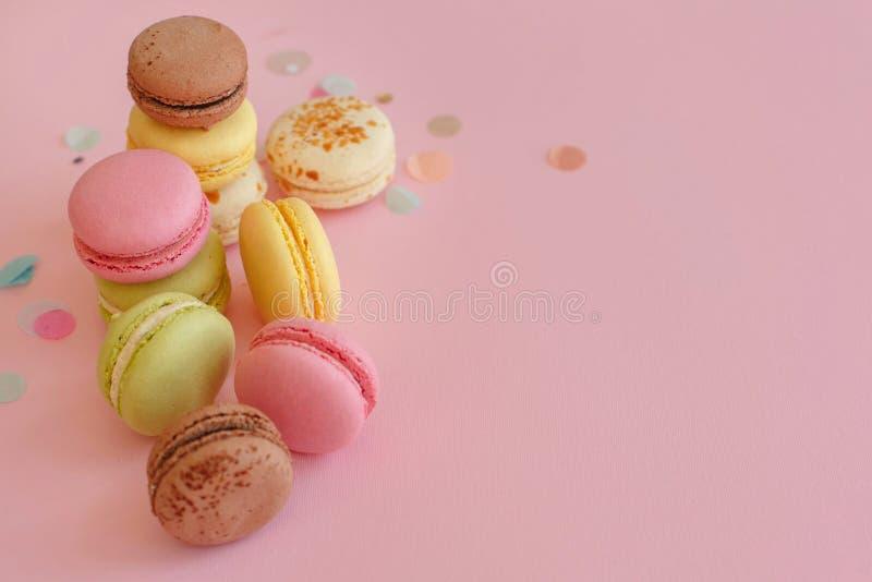 Macarons coloridos saborosos no papel na moda do rosa pastel com confett fotos de stock