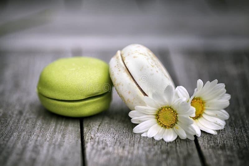 Macarons con Daisy Flowers en la tabla de madera rústica imágenes de archivo libres de regalías
