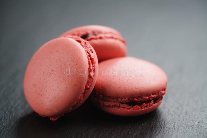 Macarons cor-de-rosa brilhantes no fundo da ardósia imagem de stock royalty free