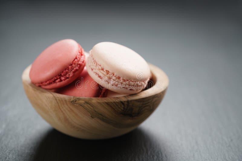 Macarons cor-de-rosa na bacia no fundo da ardósia com espaço da cópia fotografia de stock