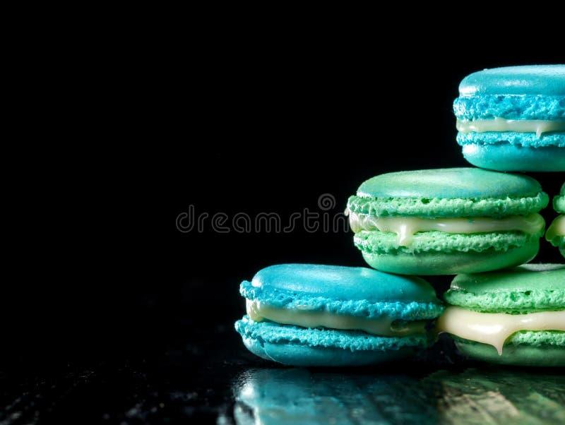 Macarons délicieux d'isolement sur le fond noir Biscuit doux français photo libre de droits