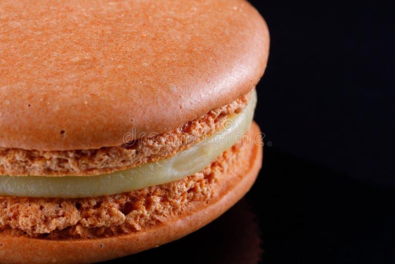 Macarons délicieux juteux lumineux de couleur sensible sur un fond noir photographie stock