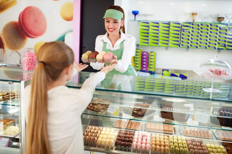 Macarons deliciosos das vendas fêmeas do pasteleiro à menina imagens de stock