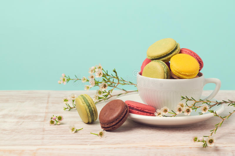 Macarons in der Kaffeetasse mit Blumen über tadellosem Hintergrund lizenzfreies stockbild
