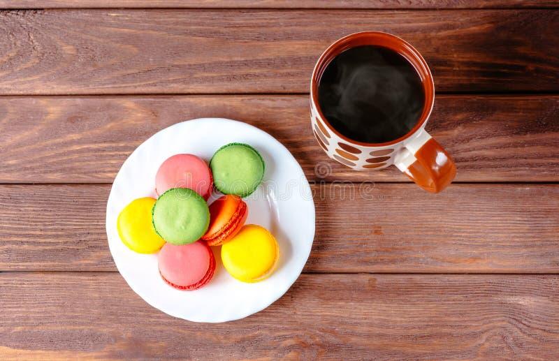 Macarons dolci variopinti e bevanda calda fotografia stock libera da diritti