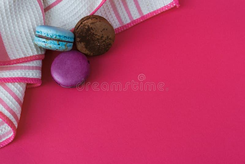 Macarons dulces Bisquits coloridos Visión superior Copie el espacio del texto Fondo de las rosas fuertes Mantel imagen de archivo