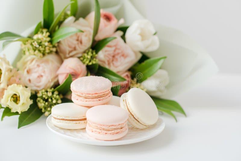 Macarons dulces elegantes y flores beige coloreadas en colores pastel imágenes de archivo libres de regalías
