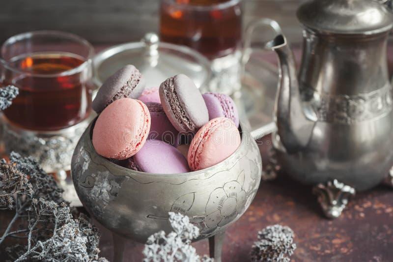 Macarons fraîchement cuits au four sur la plaque de métal avec de petites fleurs blanches et composition en appareils de thé sur  image libre de droits