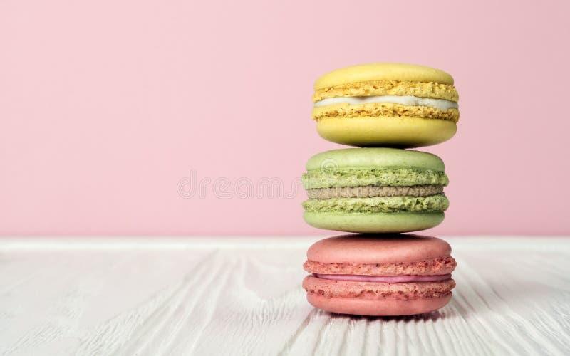 Macarons français empilés sur la table en bois et le fond rose photographie stock libre de droits
