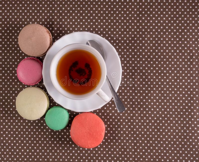 Macarons franceses coloridos com chá do copo na tabela Vista superior fotos de stock