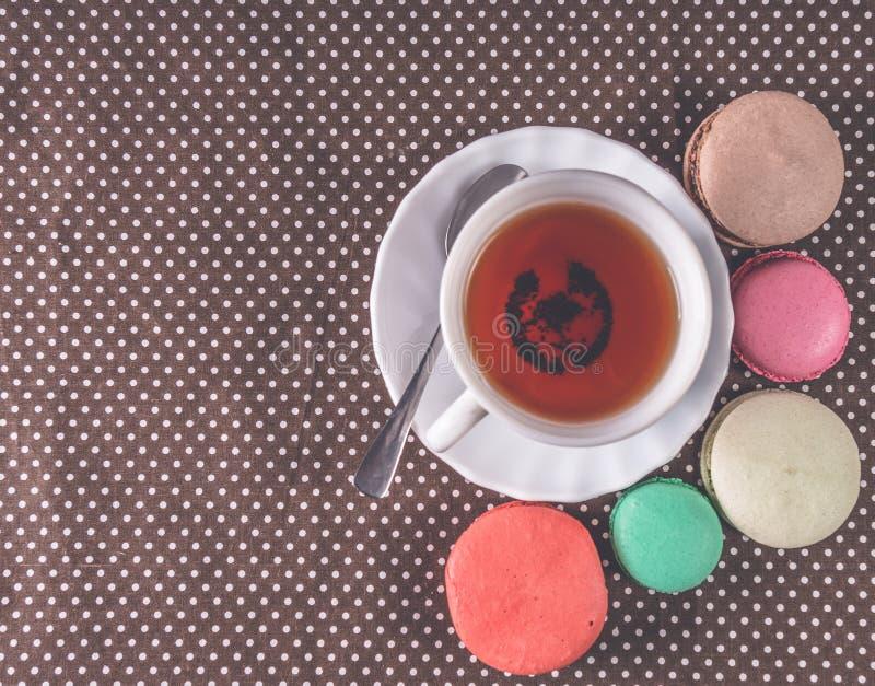 Macarons franceses coloridos con té de la taza en la tabla Visión superior imagen de archivo