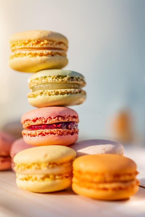Macarons franceses por la tarde del verano en el jard?n Pasteles franceses coloreados airosos dulces deliciosos Profundidad del c imagen de archivo libre de regalías