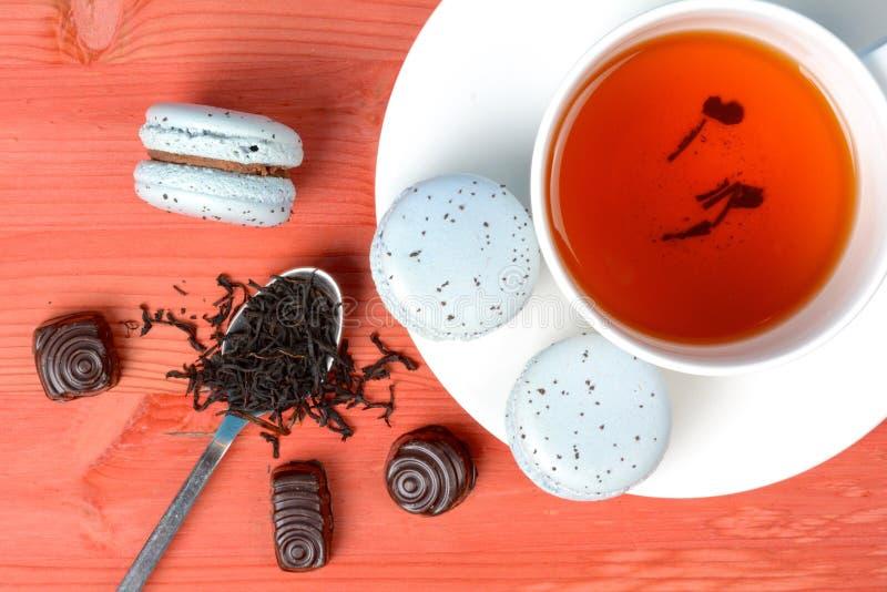 Macarons francesi blu-chiaro con il tè ed il cioccolato grigi del conte immagine stock