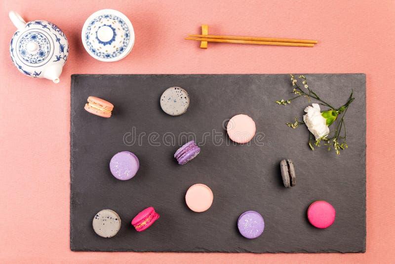 Macarons francesi e fiore bianco di incarnazione su un'ardesia, con i bastoncini e la teiera delle porcellane e la ciotola tradiz fotografia stock