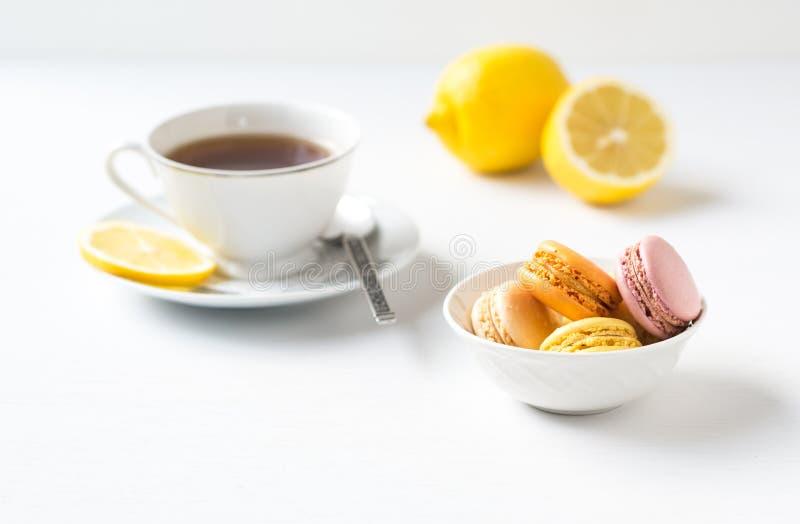 Macarons francesi variopinti con la tazza di tè. fotografie stock