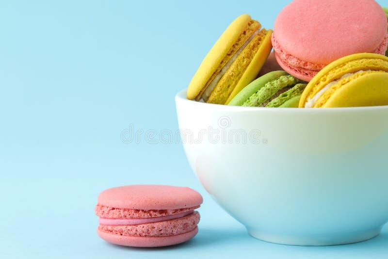 Macarons französische mehrfarbige Makronenkuchen in einer Schale kleiner franz?sischer s??er Kuchen auf hellem blauem Hintergrund stockfotos