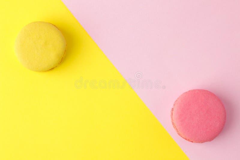 Macarons g?teaux multicolores fran?ais de macarons petit gâteau doux français sur un rose multicolore lumineux et un fond jaune D images stock