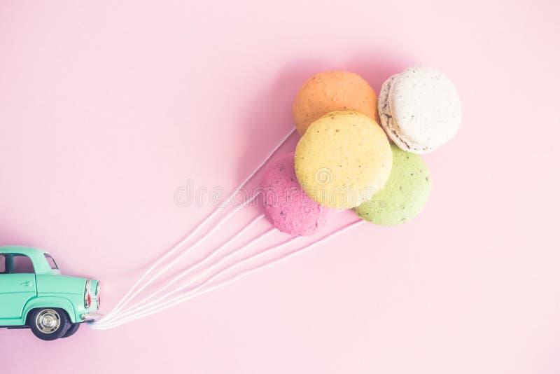 Macarons i form av ballonger fäste till den lilla retro bilen med rader arkivbilder