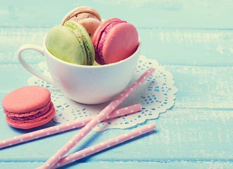 Macarons i koppen på den blåa tabellen, tonat foto arkivfoto