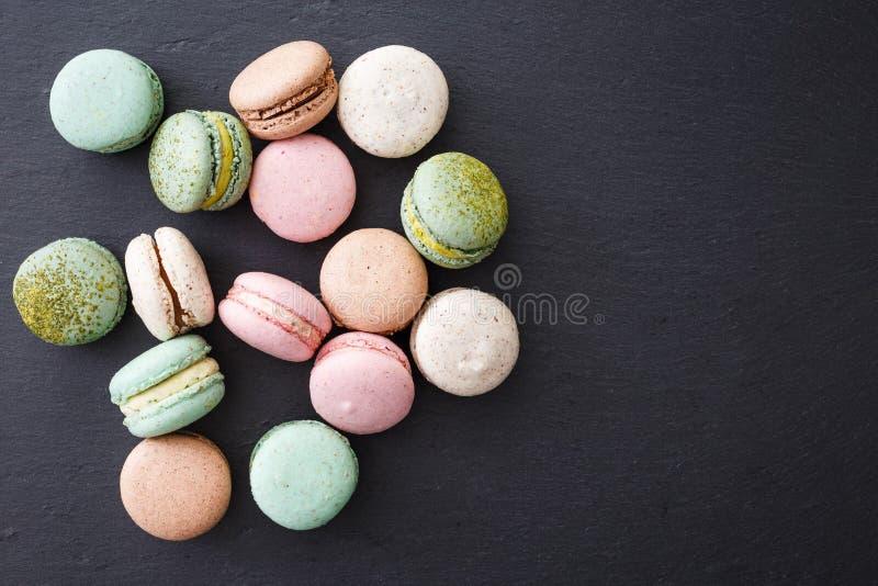 Macarons kaka, lekmanna- lägenhet för bästa sikt, makron på svart bakgrund fotografering för bildbyråer