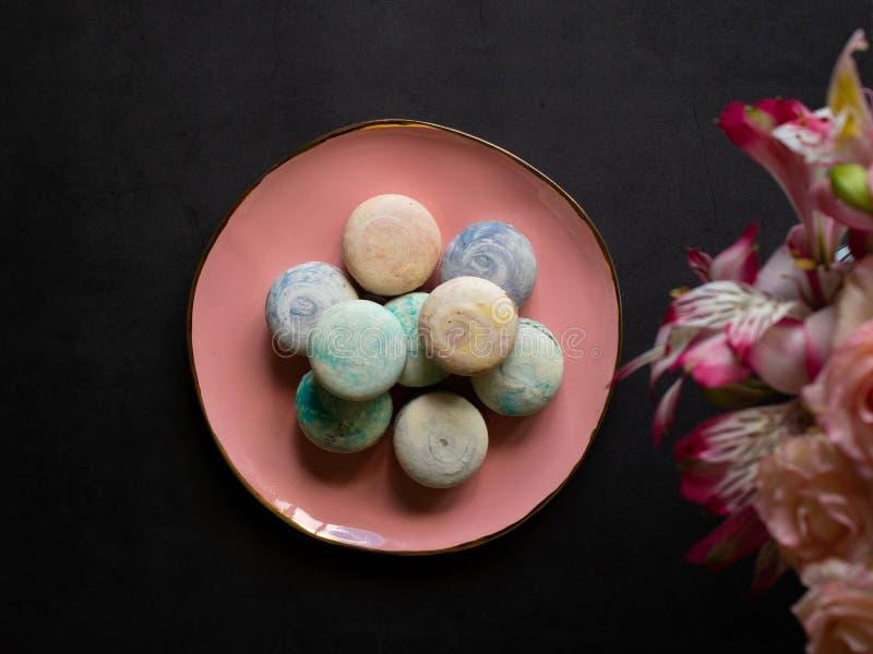 Macarons multicolores du plat rose sur une table foncée tasse blanche de thé ou de café petit déjeuner avec le dessert Bouquet de photographie stock