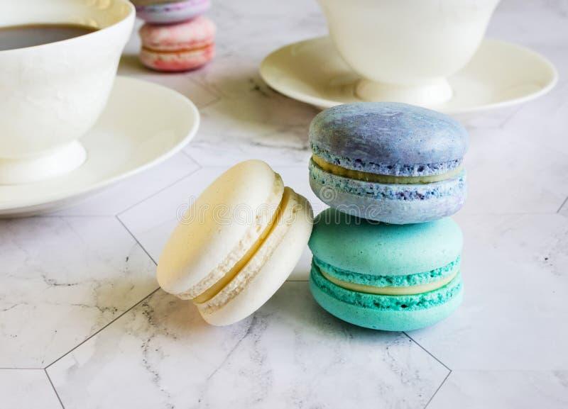 Macarons multicolores en una tabla de mármol tazas blancas de té o de café desayuno con el postre imágenes de archivo libres de regalías
