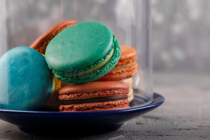 Macarons multicolores sous le dôme en verre Macarons sensibles de macarons image stock