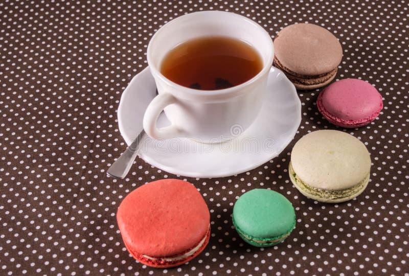 Macarons multicolori francesi dei dolci e una tazza di tè fotografia stock libera da diritti