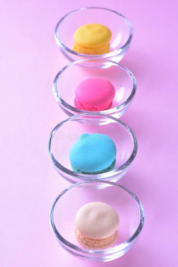 Macarons o macarrones coloridos en el beauti de cristal del dulce del postre de la taza fotos de archivo