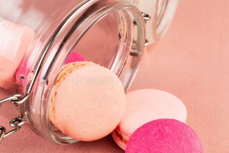 Macarons o macarrones franceses rosados, cayendo de un tarro de cristal sobre un fondo rosado del mantel, primer fotografía de archivo libre de regalías