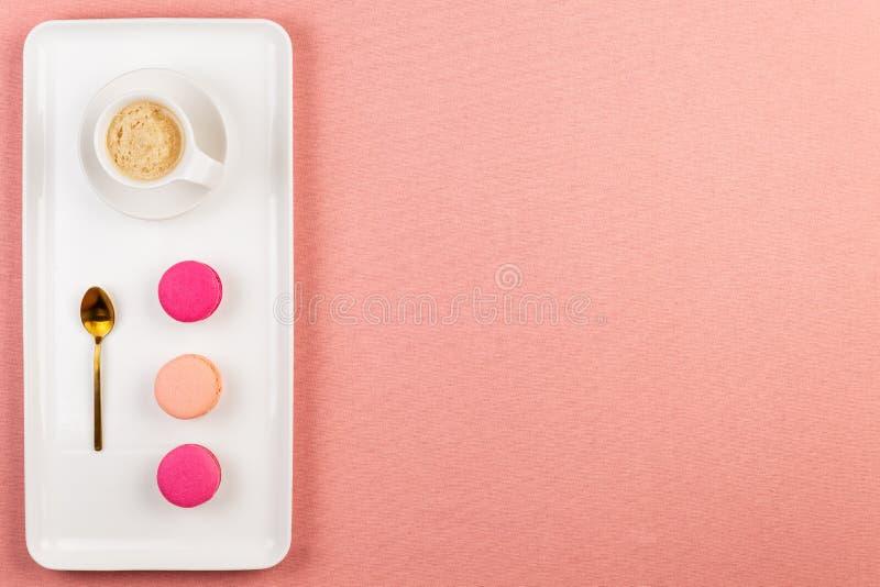 Macarons o macarrones franceses rosados, taza de café y cuchara de oro en una placa blanca del rectángulo sobre un mantel rosado  imagenes de archivo
