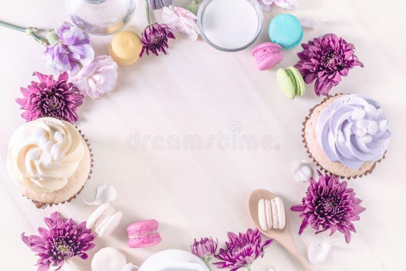 Macarons oder Makronen und kleine Kuchen mit Milch auf einem Weinlesepastell stockbild
