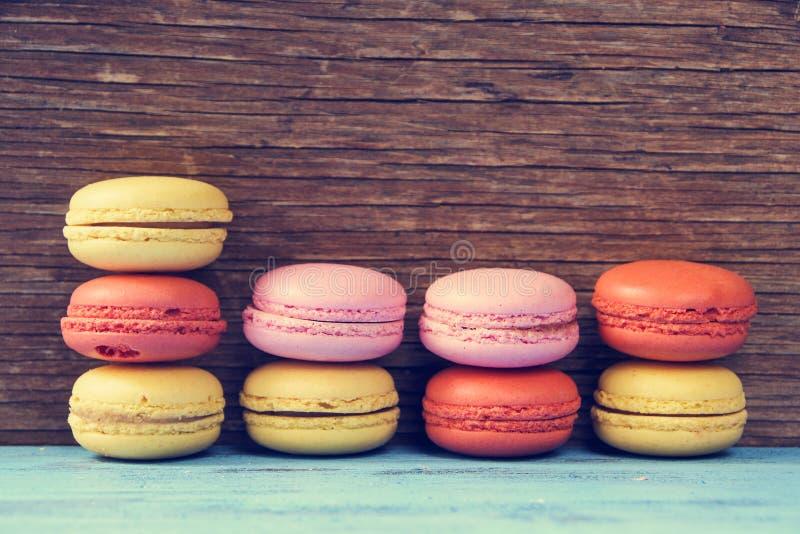 Macarons op een blauwe rustieke oppervlakte, kruist verwerkt stock foto