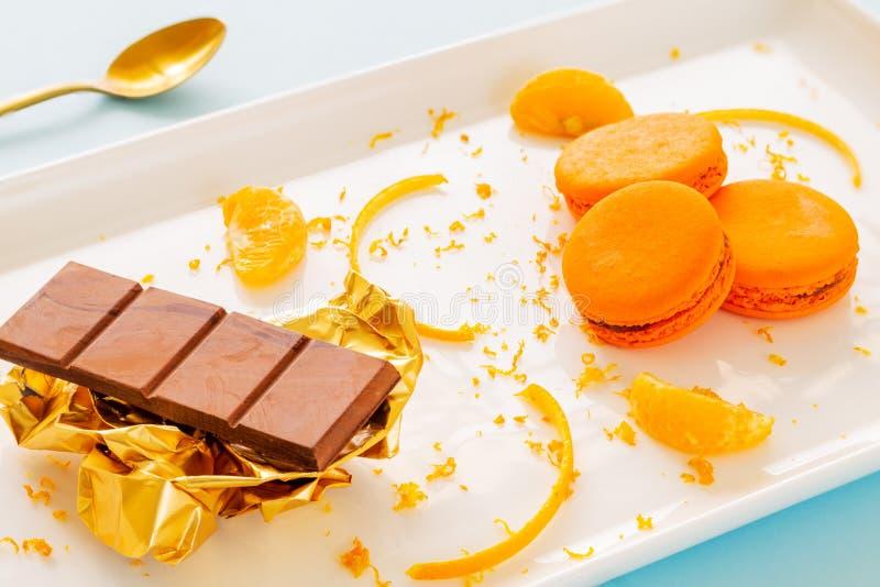 Macarons ou macarons oranges d'un plat blanc avec les peaux d'orange et la barre de chocolat au-dessus du papier d'or image stock