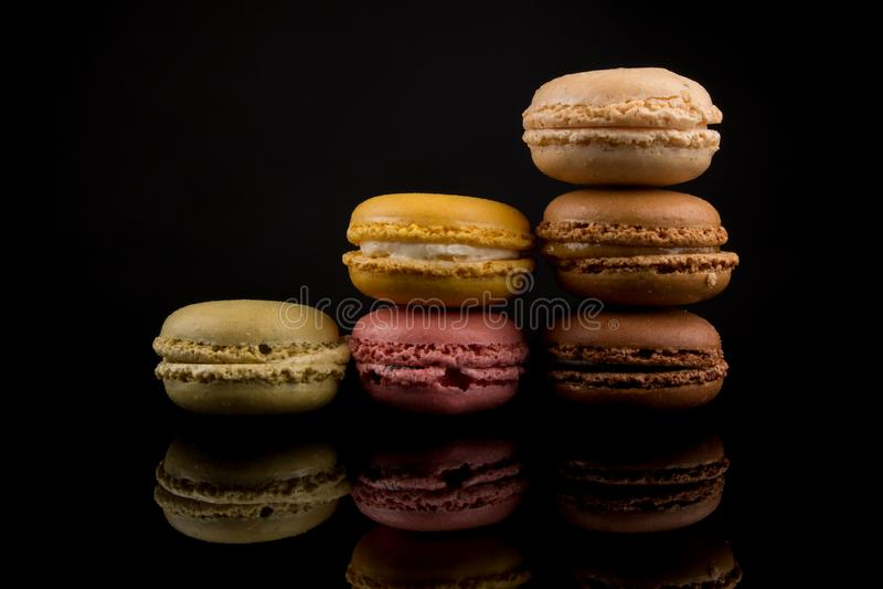Macarons, pila variopinta di Macarons, isolata su fondo nero con le riflessioni, spazio della copia, colori multipli, concentrati fotografia stock