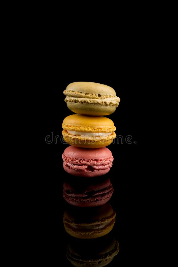 Macarons Pile, Colorful Stack of Macarons, isolated on black background with reflections, copy space royalty free stock images