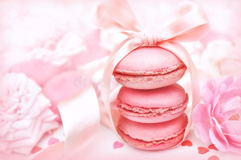 Macarons rosados en fondo suave en colores pastel de las flores de la decoración y de la rosa de la tarjeta del día de San Valent foto de archivo libre de regalías