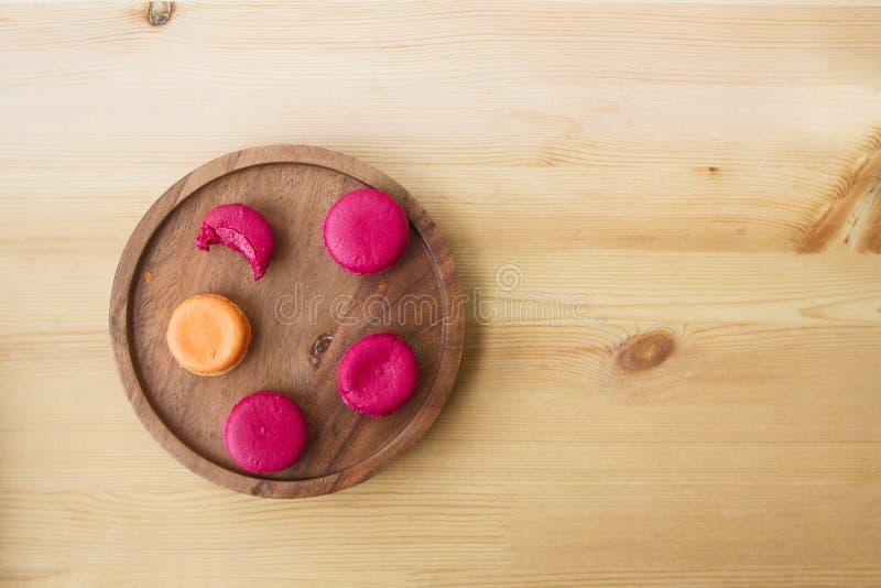 Macarons roses cramoisis de baie de framboise et de macaron français parisien orange de mangue d'un plat authentique en bois photo stock
