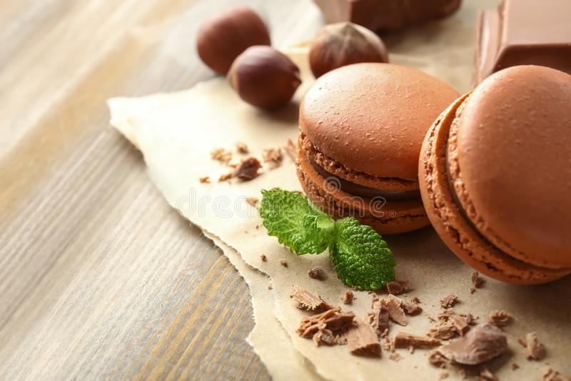 Macarons saborosos, chocolate e avelã no fundo de madeira imagem de stock