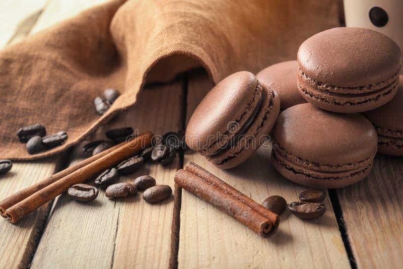 Macarons saborosos do chocolate com os feijões da canela e de café no fundo de madeira fotografia de stock