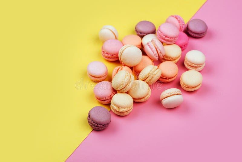Macarons sur le jaune - le fond rose s'est divisé diagonalement en deux triangles photo stock
