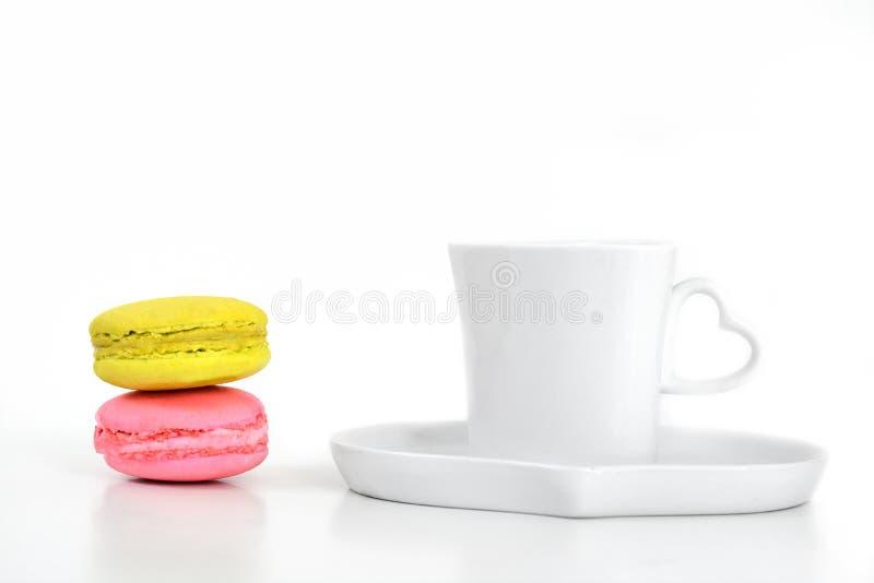 Macarons variopinti con caffè in tazza e piatto bianchi su bianco fotografia stock libera da diritti
