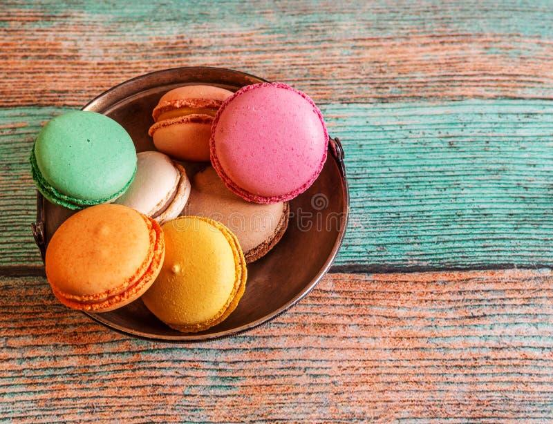 Macarons variopinti e saporiti francesi in una ciotola su una tavola di legno fotografie stock