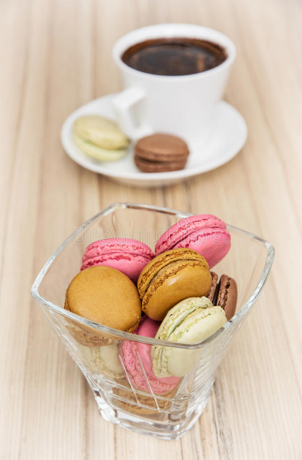 Macarons variopinti francesi con la tazza di caffè nero immagine stock